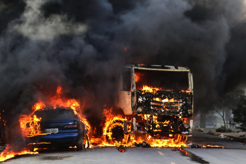 Vehicles burn in the street after attacks in the city of Fortaleza, northeastern Brazil, Thursday, Jan. 3, 2019. Brazil's newly inaugurated government has ordered military police sent to Ceara state following a wave of attacks on banks, public buildings and infrastructure over the past two days, which have hit 15 cities, including the capital. (AP Photo/Alex Gomes/O Povo)