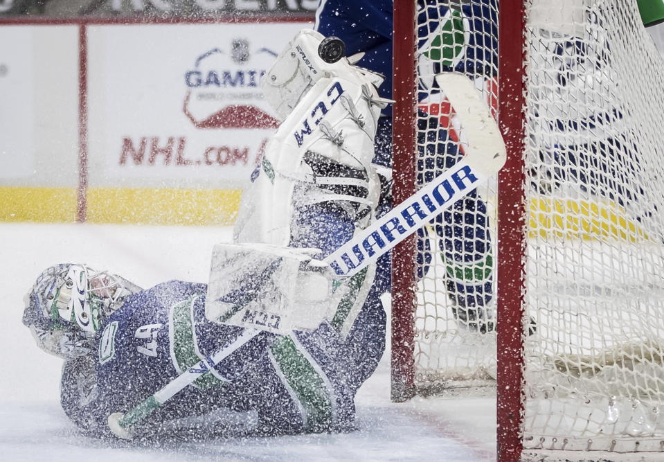 Vancouver Canucks goalie Braden Holtby stops Toronto Maple Leafs' Wayne Simmonds during the third period of an NHL hockey game in Vancouver, British Columbia, Sunday, April 18, 2021. (Darryl Dyck/The Canadian Press via AP)