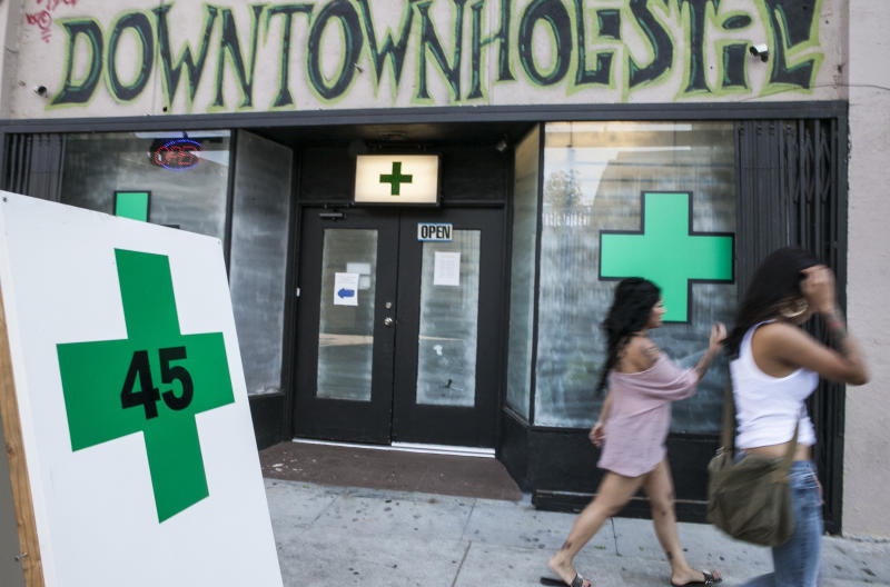 Pedestrians walk past a medical marijuana dispensary in the Echo Park area of Los Angeles Tuesday, July 24, 2012. The Los Angeles City Council on Tuesday July 24, 2012, voted to ban marijuana shops outright until it has clearer guidance from the state's highest court, after being unable to rein in the hundreds of medical marijuana dispensaries that have cropped up across the nation's second largest city. (AP Photo/Damian Dovarganes)