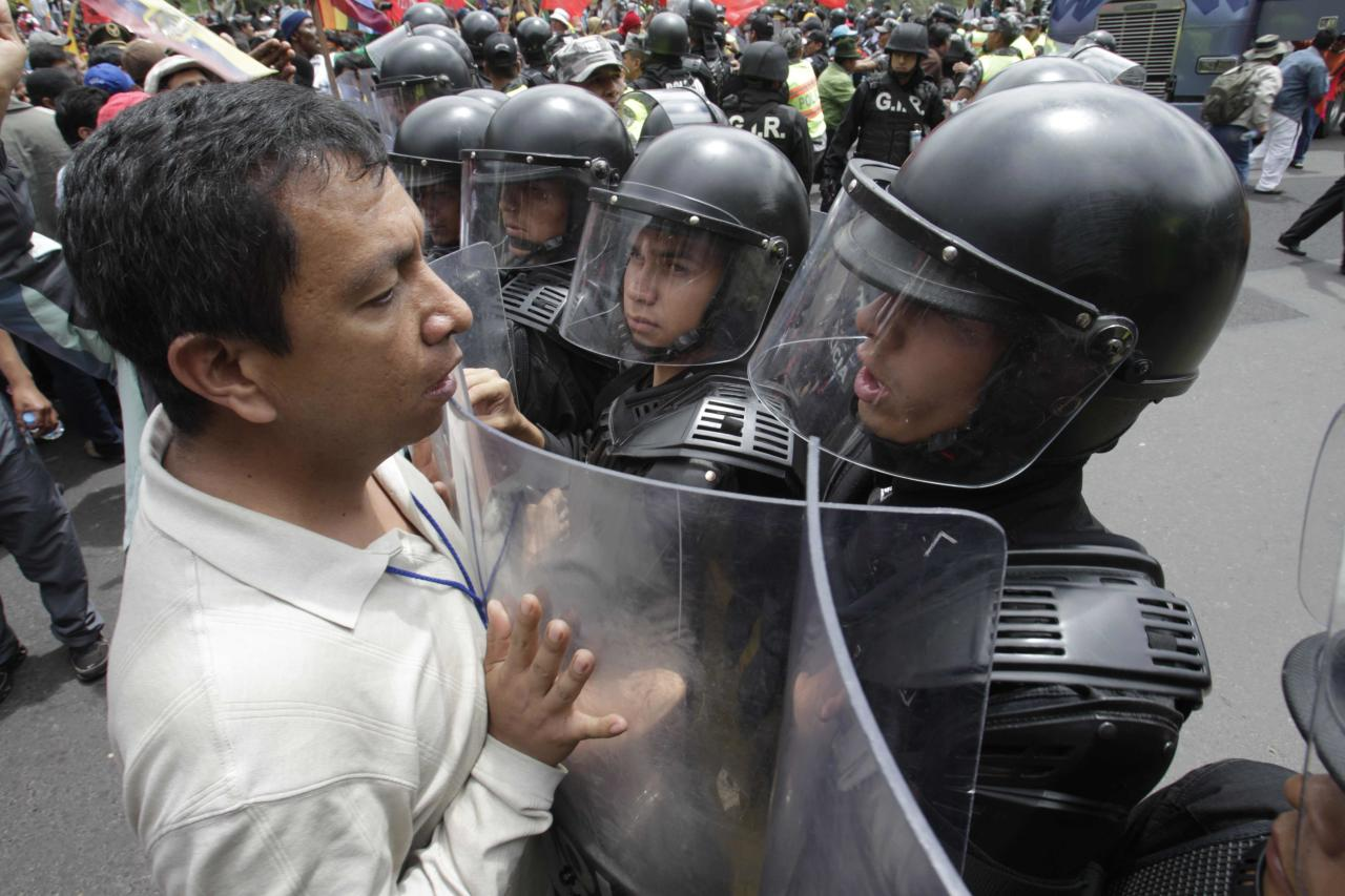 A protester confronts police during a march against President Rafael Correa's policies on mining in Quito, Ecuador, Thursday March 22, 2012. Protesters reached Ecuador's capital on Thursday after a two-week march from the Amazon to oppose plans for large-scaling mining projects on their lands. (AP Photo/Dolores Ochoa)