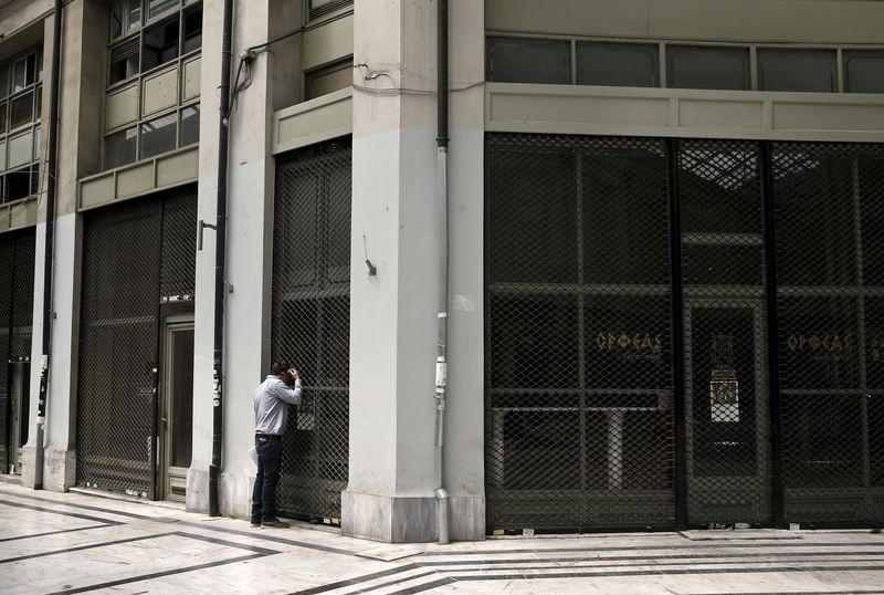 A man looks through the window of a closed shop in an arcade, where most shops closed since the beginning of the Greek financial crisis, in central Athens