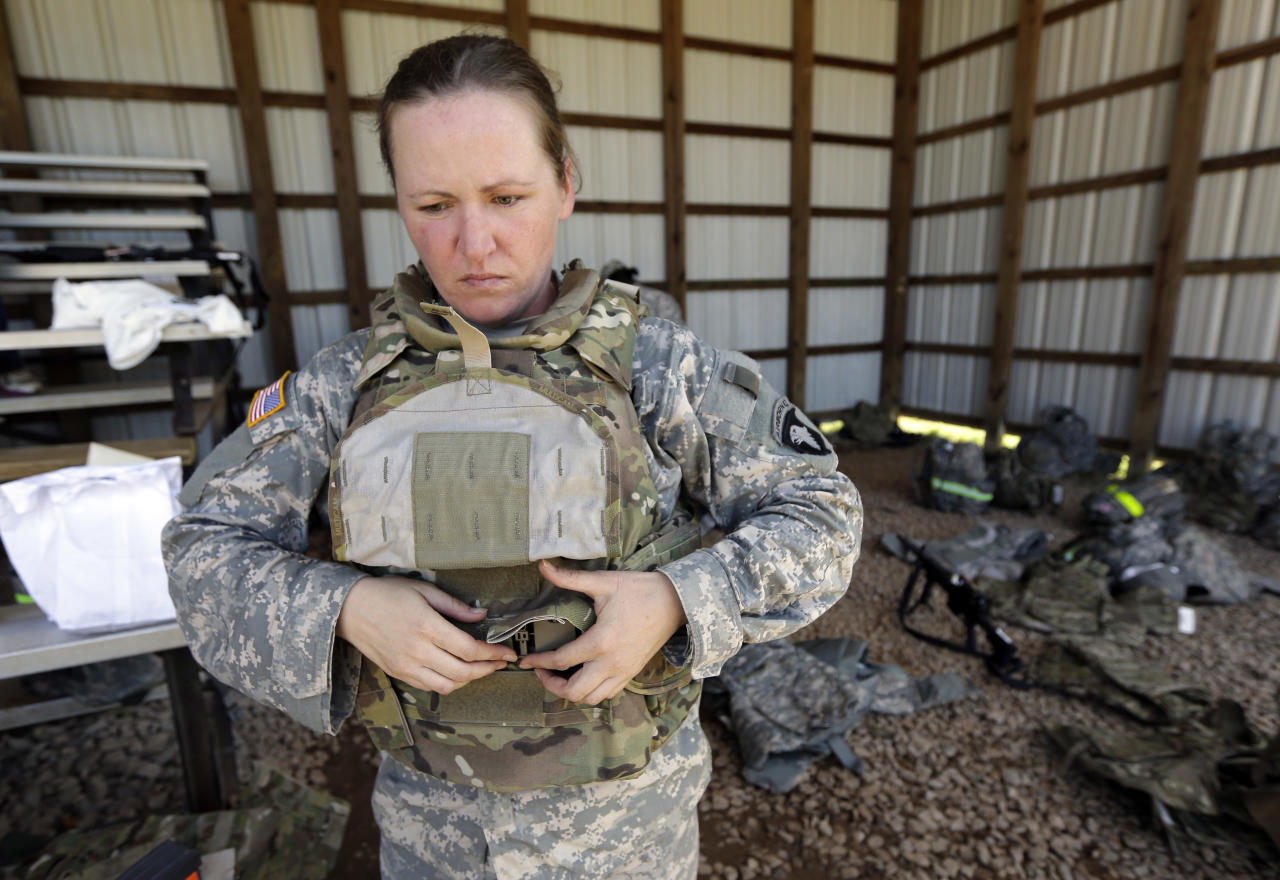 Spc. Sarah Sutphin removes her new body armor after training on a firing range on Tuesday, Sept. 18, 2012, in Fort Campbell, Ky. Female soldiers from 1st Brigade Combat Team, 101st Airborne Division are field testing the first Army body armor designed to fit women's physiques in preparation for their deployment to Afghanistan this fall. (AP Photo/Mark Humphrey).