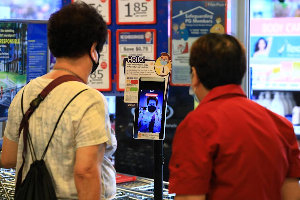SINGAPORE - JUNE 19:  A woman wearing a protective mask has her temperature taken using a contactless temperature scanner before checking-in at a supermarket on June 19, 2020 in Singapore. Today, Singapore starts to further ease the coronavirus (COVID-19) restrictions by allowing social gatherings up to five people, re-opening of retail outlets and dining in at food and beverage outlets, subjected to safe distancing. Parks, beaches, sports amenities and public facilities in the housing estates will also reopen. However, large scale events, religious congregations, libraries, galleries and theaters will remain closed.  (Photo by Suhaimi Abdullah/Getty Images)