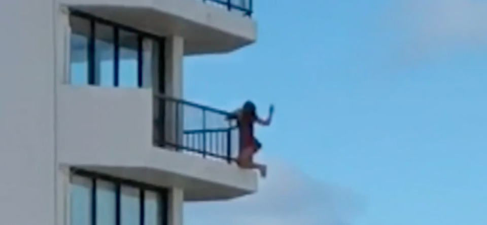 A woman holds out one of her arms while using the other to cling to the outside of a balcony railing.