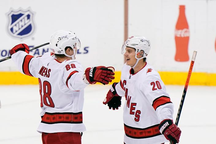 Hurricanes center Martin Necas (88) is congratulated by center Sebastian Aho after Necas scored the winning goal in OT to beat the Panthers on Monday.