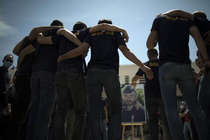 Police officers console each other during a ceremony to commemorate a slain colleague at a police station in Avignon, southern France, Sunday, May 9, 2021. Police officers and civilians gathered to commemorate the death of a police officer who was killed Wednesday at a known drug-dealing site in the southern France city of Avignon. (AP Photo/Daniel Cole)
