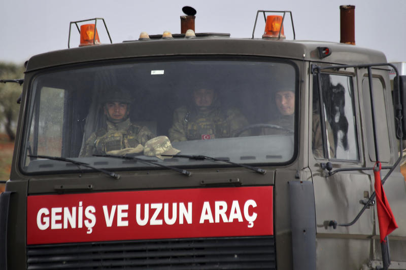 Turkish soldiers inside a military truck as a military convoy drives through the village of Binnish, in Idlib province, Syria, Saturday, Feb. 8, 2020. Several Turkish armored vehicles and tanks entered rebel-controlled northwestern Syria since Friday, the latest reinforcements sent in by Ankara amid a Syrian government offensive that this week brought the two countries' troops into a rare direct confrontation. (AP Photo/Ghaith Alsayed)