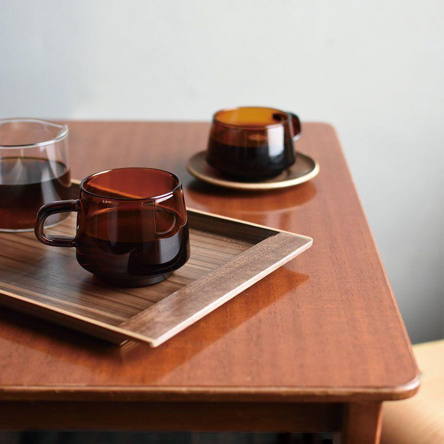 """<p>Invest in new mugs and you can imagine you're sat in a stylish café rather than your own kitchen. These sepia-toned glass mugs come in two sizes, and there is even a matching walnut tray with room for biscuits. £19.50 each, <a href=""""https://kinto-europe.com/products/21741"""" rel=""""nofollow noopener"""" target=""""_blank"""" data-ylk=""""slk:kinto-europe.com"""" class=""""link rapid-noclick-resp"""">kinto-europe.com</a></p>"""