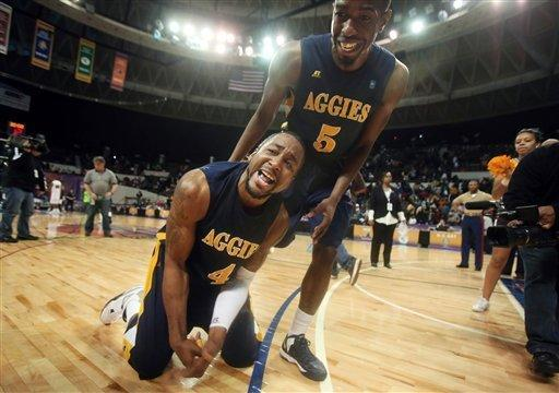 North Carolina A&T's DaMetrius Upchurch, bottom and Jean Louisme celebrate after Morgan State 57-54 in an NCAA college basketball game in the championship of the Mid-Eastern Athletic Conference tournament, Saturday, March 16, 2013, in Nofolk, Va. (AP Photo/The Virginian-Pilot, Steve Earley)