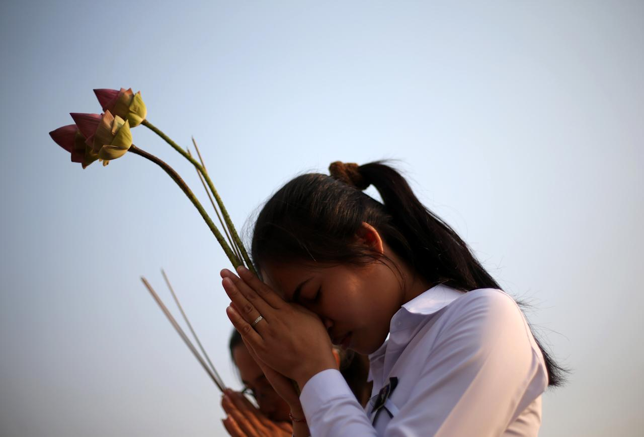 Two girls offer prayers to Cambodia's former King Norodom Sihanouk in Phnom Penh, Monday, Feb. 4, 2013. Sihanouk's body had been lying in state at the Royal Palace after being flown from Beijing where he died Oct. 15 of a heart attack at the age of 89. The cremation, the climax of seven days of mourning, will take place Monday. (AP Photo/Wong Maye-E)