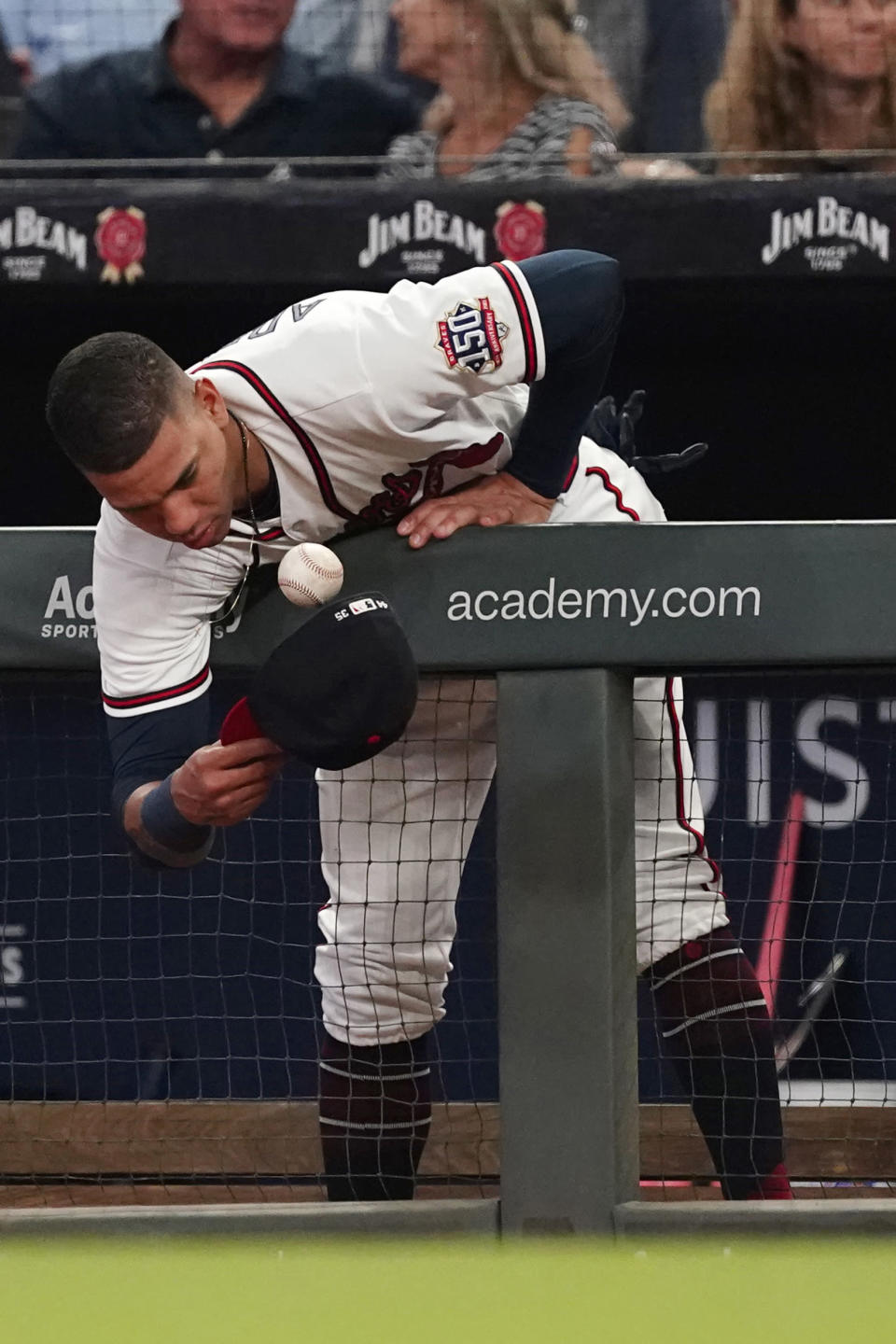 Atlanta Braves' Ehire Adrianza (23) leans over the dugout railing to catch a foul ball in his hat during a baseball game against the Philadelphia Phillies Tuesday, Sept. 28, 2021, in Atlanta. (AP Photo/John Bazemore)