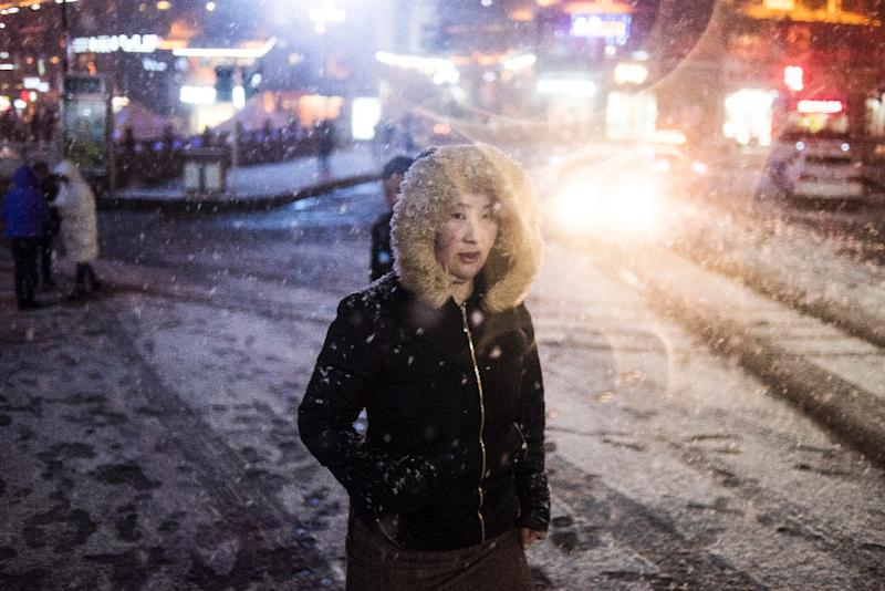 A woman walks in the snow in Kangding in the Ganzi Tibetan Autonomous Prefecture, southwestern China (AFP Photo/Fred Dufour)