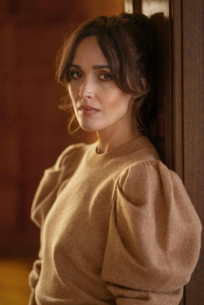 Closeup of Rose Byrne in a sweater with puffed sleeves.