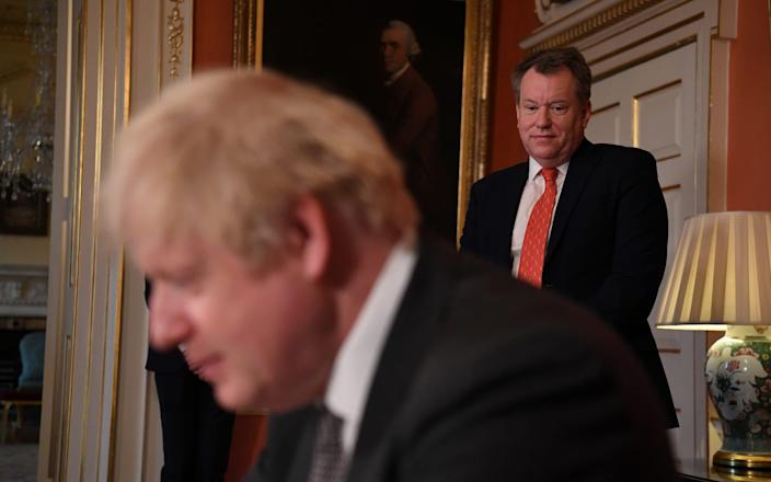 David Frost looks on as Boris Johnson signs the Brexit trade deal - Reuters