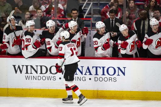 New Jersey Devils center Nico Hischier (13), from Switzerland, high-fives his teammates after scoring during the first period of the team's NHL hockey game against the Washington Capitals, Saturday, Jan. 11, 2020, in Washington. (AP Photo/Al Drago)