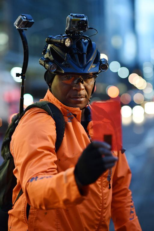 London 'carriageway vigilante', cyclist Lewis Dediare, brandishes his red card in London on December 15, 2014 (AFP Photo/Leon Neal)