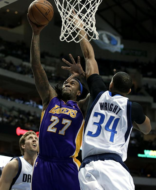 Los Angeles Lakers' Jordan Hill (27) goes up for a shot against Dallas Mavericks' Brandan Wright (34) as Dirk Nowitzki, left rear, watches in the first half of an NBA basketball game, Tuesday, Jan. 7, 2014, in Dallas. (AP Photo/Tony Gutierrez)