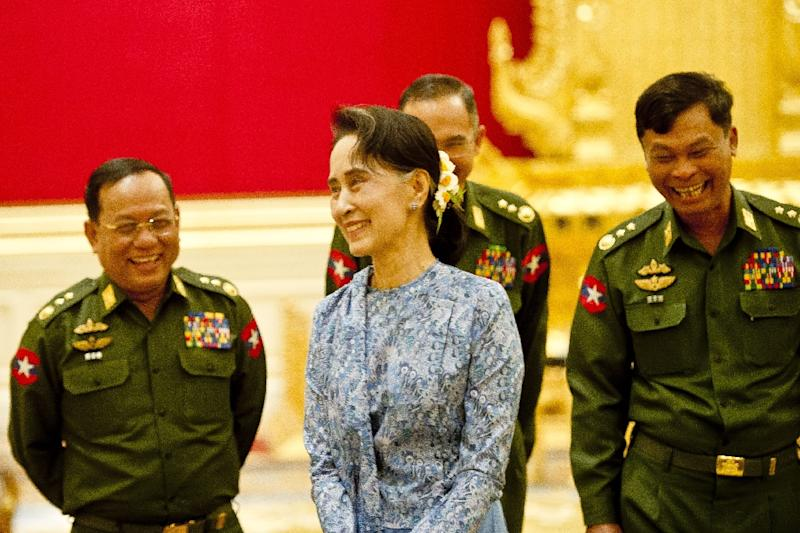 Newly sworn-in Myanmar's Foreign Minister Aung San Suu Kyi shares a light momemt with generals during the handover ceremony at the presidential house in Naypyidaw, on March 30, 2016 (AFP Photo/Ye Aung Thu)