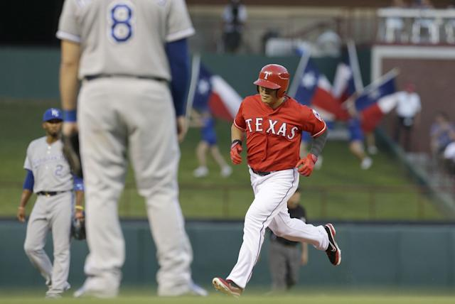Texas Rangers Shin-Soo Choo, right, runs the bases after a solo home run as Kansas City Royals third baseman Mike Moustakas (8) and shortstop Alcides Escobar (2) look on during the first inning of a baseball game Saturday, Aug. 23, 2014, in Arlington, Texas. (AP Photo/LM Otero)