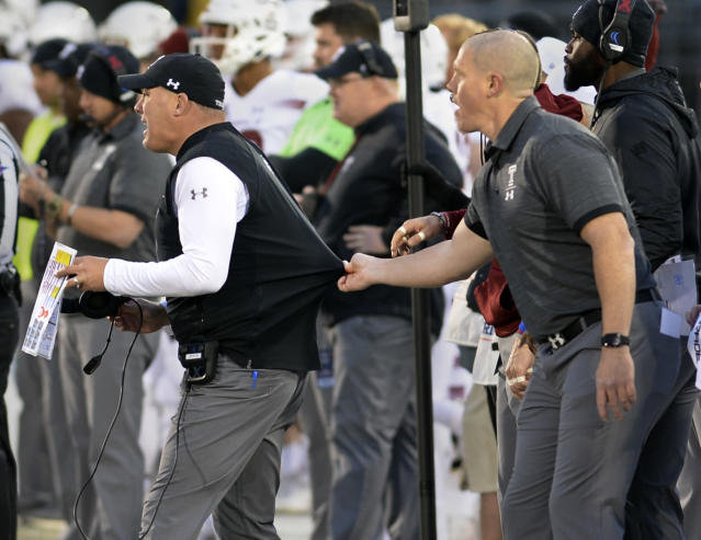 Temple head coach Geoff Collins, left, is held back by his assistant during the first half of an NCAA college football game against Connecticut, Saturday, Nov. 24, 2018, in East Hartford, Conn. (AP Photo/Stephen Dunn)