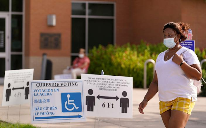 A woman leaves a polling place in Houston - Melissa Phillip/Houston Chronicle via AP