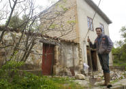 Cain Burdeau stands in front of former barns in Castelbuono, Sicily, on April 13, 2021, that he plans to convert into a family home. (AP Photo/Audrey Rodeman)