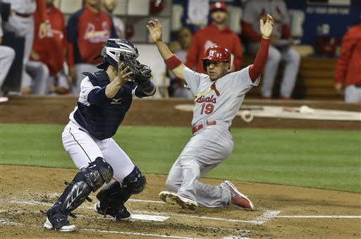 St. Louis Cardinals' Jon Jay slides into home as San Diego Padres catcher John Baker takes in a late throw in the fifth inning of a baseball game in San Diego, Tuesday, May 21, 2013. (AP Photo/Lenny Ignelzi)