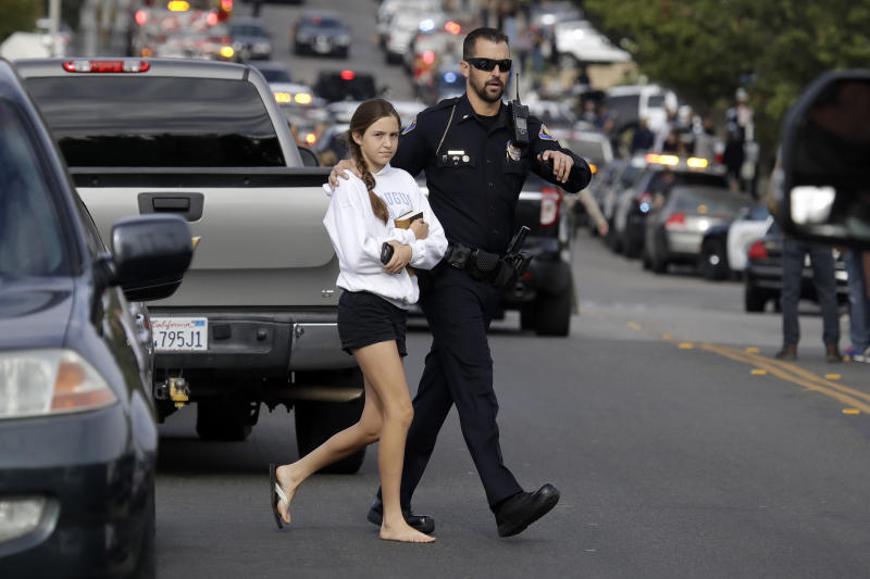 A student is escorted out of Saugus High School after reports of a shooting on Nov. 14, 2019, in Santa Clarita, Calif. (Photo: Marcio Jose Sanchez/AP)