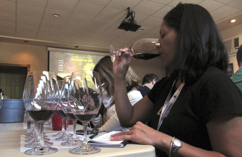 Annette Alvarez-Peters, assistant general manager for Costco Wholesale Corp., sips a syrah on Wednesday, Sept. 29, 2010, during a road trip of Washington wine country in Wapato, Wash. (AP Photo/Shannon Dininny)