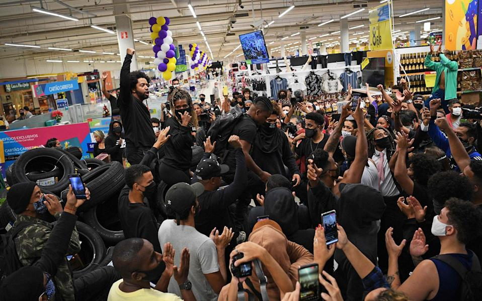 Demonstrators make a barrier out of car tyres as they take part in a protest inside the supermarket Carrefour - AFP