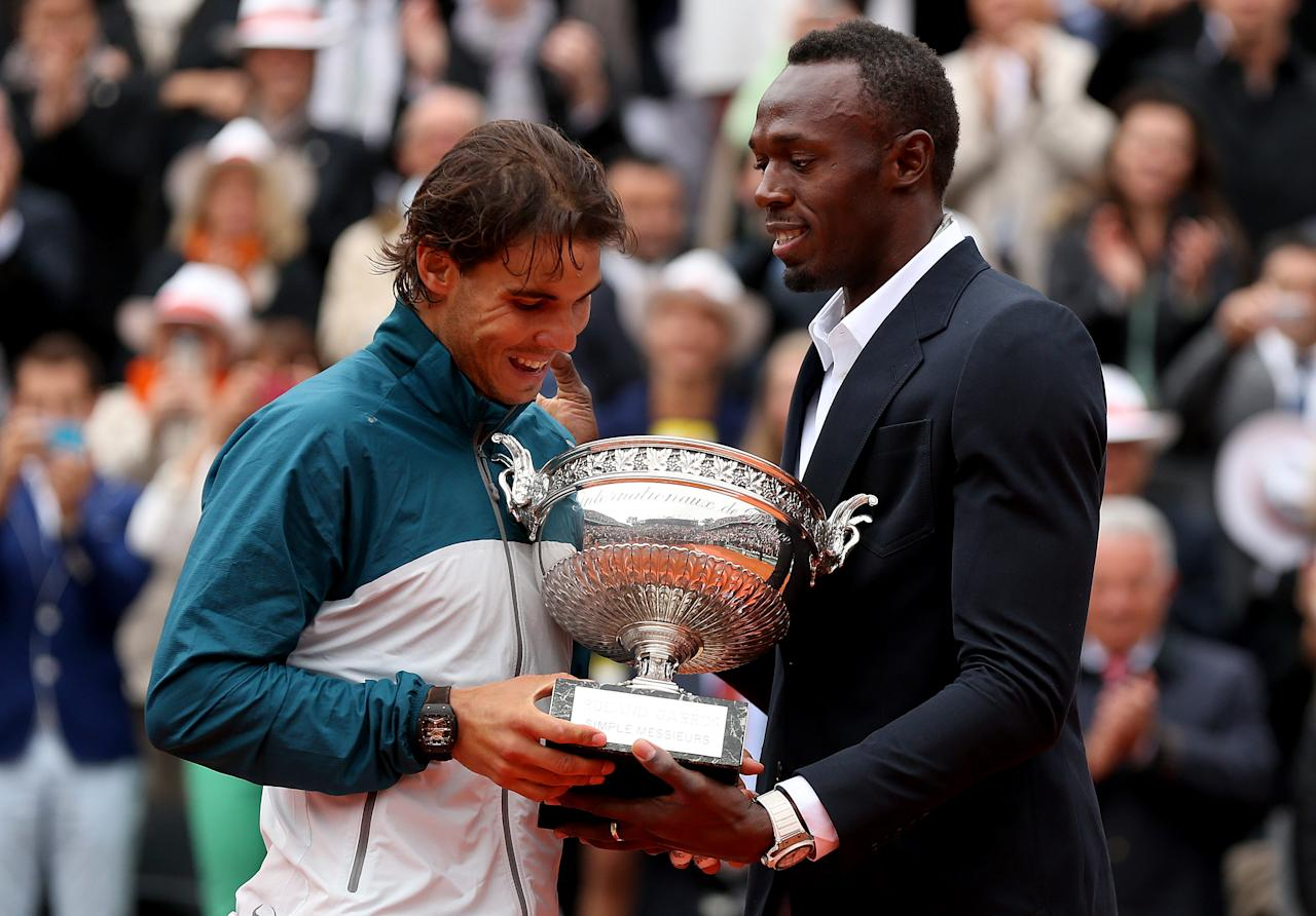 PARIS, FRANCE - JUNE 09:  Rafael Nadal of Spain is presented with the Coupe des Mousquetaires trophy by Usian Bolt after the men's singles final against David Ferrer of Spain during day fifteen of the French Open at Roland Garros on June 9, 2013 in Paris, France.  (Photo by Matthew Stockman/Getty Images)