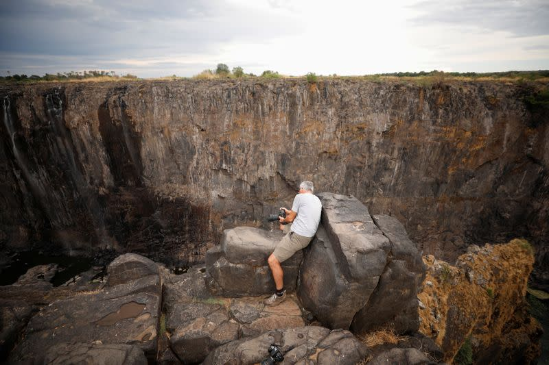Visitors take pictures before dry cliffs following a prolonged drought at Victoria Falls