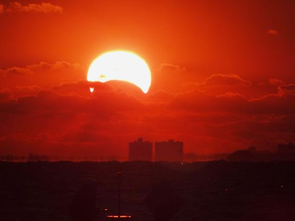 Photographer James Currie captured this view of the sunrise partial solar eclipse over Norfolk, Va., on Nov. 3, 2013 during a rare hybrid solar eclipse. 'This was the first time I got to see a solar eclipse!' Currie told SPACE.com.