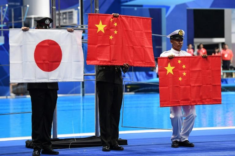 Officials had to hold up the Chinese and Japanese flags after they fell down during a victory ceremony at the Asian Games swimming pool