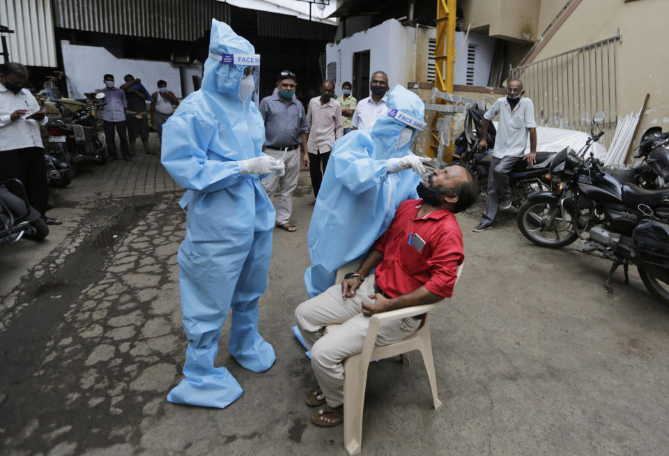 A health worker takes a nasal swab sample to test for COVID-19 in Ahmedabad, India, Friday, Sept. 11, 2020. India's coronavirus cases are now the second-highest in the world and only behind the United States. (AP Photo/Ajit Solanki)