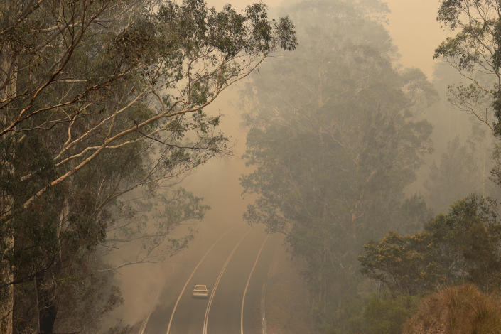 Smoke from wildfires shrouds a road near Moruya, Australia, Saturday, Jan. 4, 2020. Australia's Prime Minister Scott Morrison called up about 3,000 reservists as the threat of wildfires escalated Saturday in at least three states with two more deaths, and strong winds and high temperatures were forecast to bring flames to populated areas including the suburbs of Sydney. (AP Photo/Rick Rycroft)