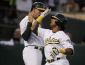 Oakland Athletics' Khris Davis, right, celebrates with Stephen Piscotty after hitting a two-run home run off New York Yankees' J.A. Happ during the second inning of a baseball game Wednesday, Aug. 21, 2019, in Oakland, Calif. (AP Photo/Ben Margot)