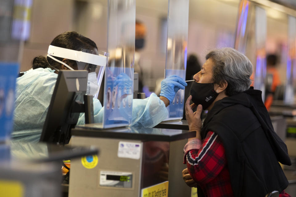 A traveler is tested for COVID-19 in Tom Bradley International at LAX  on Nov. 17, 2020 in Los Angeles, CA. Los Angeles International Airport started issuing molecular or PCR tests  this week and has plans to quickly expand the program in order to help detect coronavirus and slow its spread. (Francine Orr/Los Angeles Times via Getty Images)