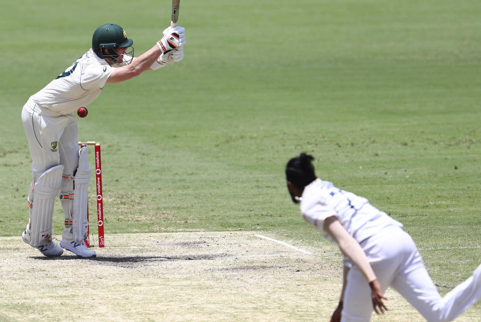 Australia's Steve Smith is hit while batting during play on day four of the fourth cricket test between India and Australia at the Gabba, Brisbane, Australia, Monday, Jan. 18, 2021. (AP Photo/Tertius Pickard)