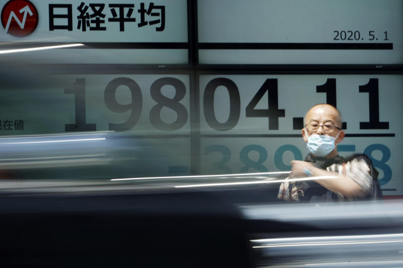 A man stands in front of an electronic stock board showing Japan's Nikkei 225 index at a securities firm in Tokyo Friday, May 1, 2020. Shares have dropped in Asia after Wall Street ended its best month in 33 years with losses on fresh news of economic carnage from the coronavirus pandemic. (AP Photo/Eugene Hoshiko)