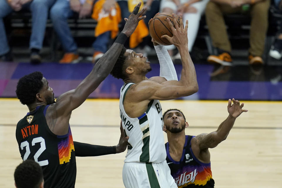 Milwaukee Bucks forward Giannis Antetokounmpo, middle, shoots between Phoenix Suns center Deandre Ayton (22) and guard Cameron Payne during the first half of Game 5 of basketball's NBA Finals, Saturday, July 17, 2021, in Phoenix. (AP Photo/Ross D. Franklin)