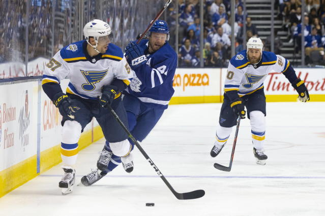 St. Louis Blues left wing David Perron (57) looks to play a pass under pressure from Toronto Maple Leafs defenseman Morgan Rielly (44) during first-period NHL hockey game action in Toronto, Monday, Oct. 7, 2019. (Chris Young/The Canadian Press via AP)