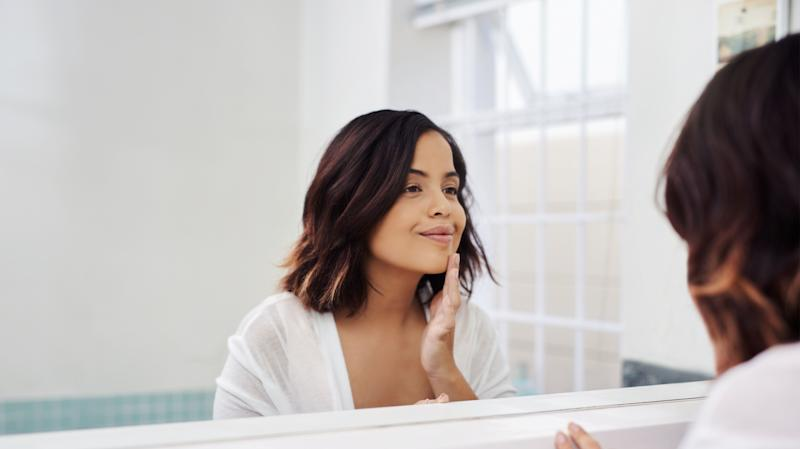 Shot of an attractive young woman going through her morning beauty routine in the bathroom