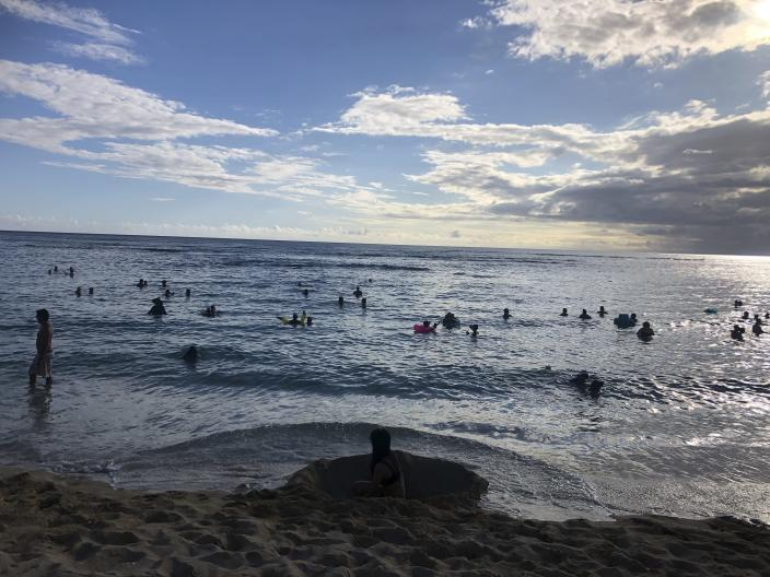 In this photo taken May 13, 2020 in Honolulu, people are in the water at a Waikiki beach. A group of people are helping track down violators of a 14-day quarantine on travelers arriving to Hawaii. (AP Photo/Jennifer Sinco Kelleher)