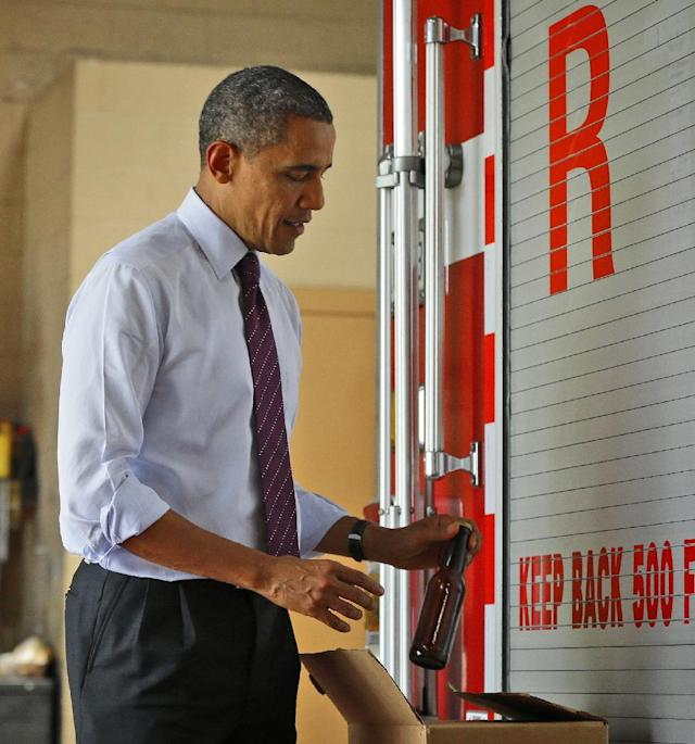 President Barack Obama pulls out a bottle of beer as he delivers a case of White House brewed beer to the fire fighters at Fire Station No. 14, during an unscheduled stop, Tuesday, Sept. 4, 2012, in Norfolk, Va. (AP Photo/Pablo Martinez Monsivais)