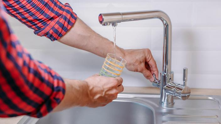 Man pouring glass of water from tap with clean filter in kitchen, close up stock photo