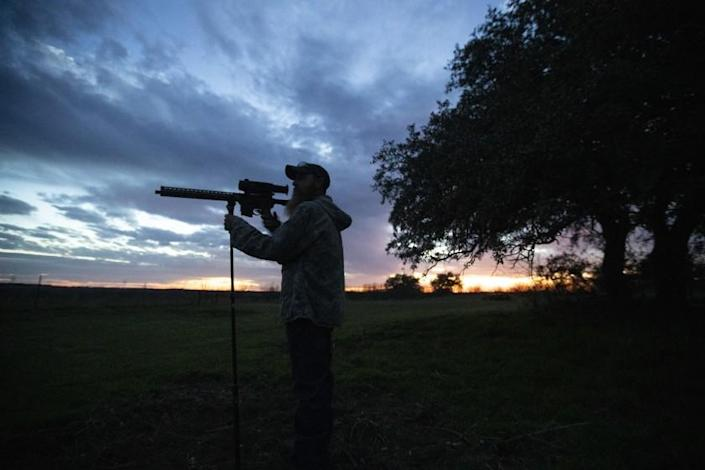THROCKMORTON COUNTY, TEXAS -- SATURDAY, FEBRUARY 29, 2020: Fred Jones peers through the infrared scope on his AR-style rifle as night falls on a wheat field in rural Throckmorton County, Texas, on Feb. 29, 2020. (Brian van der Brug / Los Angeles Times)