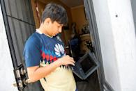 Angel, 13, stands outside his home trying to connect his computer to the wifi hotspot provided by a parked van from JFK company in order to follow his online classes in Santa Ana, California
