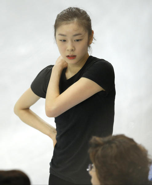 Figure skater Yuna Kim of South Korea speaks with team members in the practice rink at the 2014 Winter Olympics, Thursday, Feb. 13, 2014, in Sochi, Russia. (AP Photo/Vadim Ghirda)