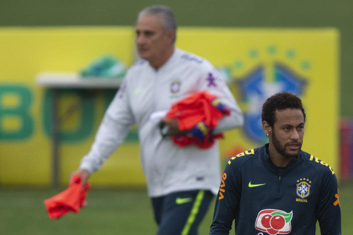 Brazil's soccer player Neymar attends a team practice session lead by national team coach Tite, behind, at the Granja Comary training center ahead the Copa America tournament in Teresopolis, Brazil, Sunday, June 2, 2019. (AP Photo/Leo Correa)
